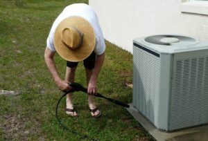 man performing ac maintenance on outside unit