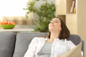 woman on couch enjoying benefits of ductless ac